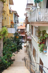 Narrow street in Alanya, steep stairs and balconies with flowers, Turkey, April 2021, cityscape