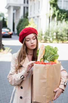 young woman in beige trench coat and red beret looking at paper bag with groceries on urban street