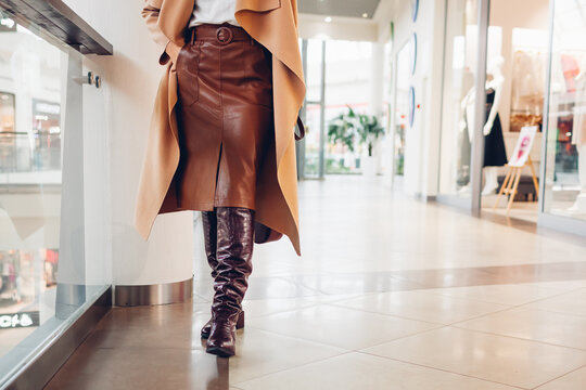 Autumn fashion. Stylish woman wearing trendy high boots, leather skirt walking in shopping center holding purse.