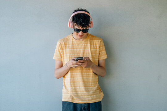 teenage boy with headphones and mobile phone on the wall