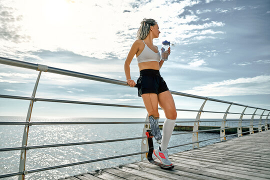 Young disabled athlete woman with prosthetic leg standing on the bridge near the sea and drinking water from a bottle.