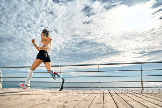 Take care of your body. Side view of a strong disabled woman in sportswear with a prosthetic leg is running on the bridge.