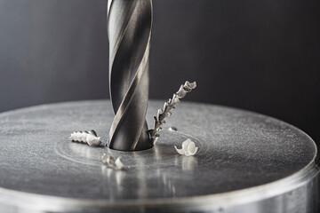 Fototapeta metal drill bit make holes in steel billet on industrial drilling machine. Metal work industry. multi cutting tool and end mill. obraz