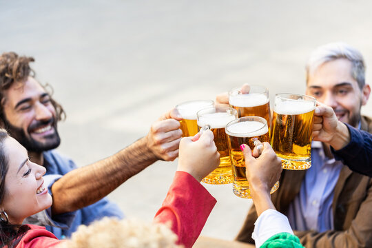 Group of multiracial friends cheering with beers in terrace bar - Happy diverse young college students having fun together while drinking alcohol after class in university campus - Friendship concept