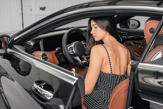 Young asian woman sitting in luxury car in garage before starting engine