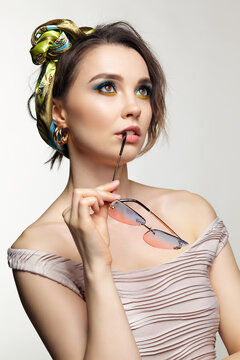 Portrait of young woman gnaws at the shackle of glasses.