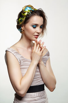 Portrait of young woman with eyes closed. Female posing in headscarf with hand near face.