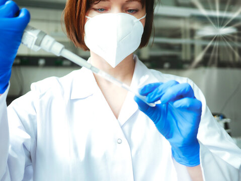 Scientist or laboratory researcher in a protective mask and laboratory gloves holds a laboratory pipette and pipets a sample into a test tube. Medical diagnostics, research and science background.