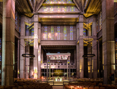 Le Havre, France - June 7, 2021: Front view of the altar in the center of St Joseph church built in 1957 after french architect Auguste Perret and illuminated through stained glass by Marguerite Hure.