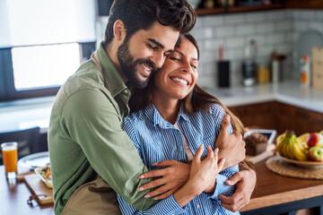 Obraz Happy couple in love having fun in kitchen at home - fototapety do salonu