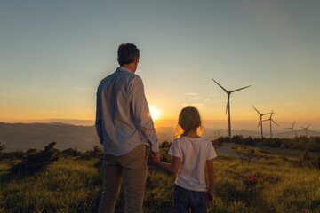 Obraz Cinematic shot of carefree young father engineer keeping his daughter for hand and looking on windmill field at sunset. Concept of renewable energy, love for nature, family, electricity, green, future - fototapety do salonu