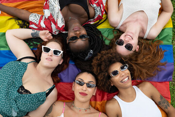 Fototapeta Cinematic shot of girl friends of different ethnicities with sunglasses while lying on LGBT rainbow flag in park. Concept of friendship, homophobia, diversity, equality, freedom, liberty, multiethnic. obraz
