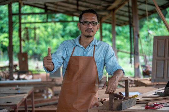 Thumb up of portrait man carpenter enjoying working