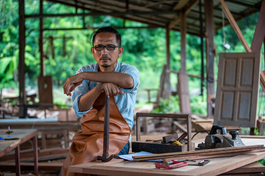 portrait man carpenter enjoying working in the factory