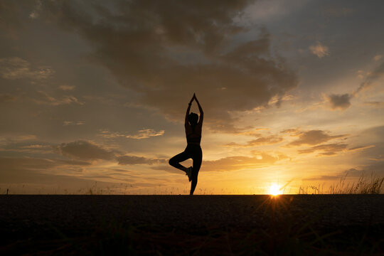silhouette of women exercising with yoga poses