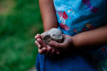 Kamień trzymany w rękach przez dziewczynkę