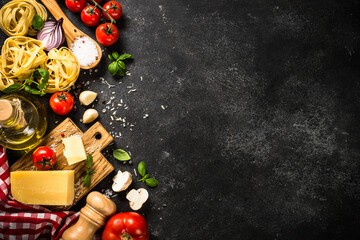 Italian food background black table. Raw Pasta, fresh tomatoes, olive oil, parmesan, spices and...