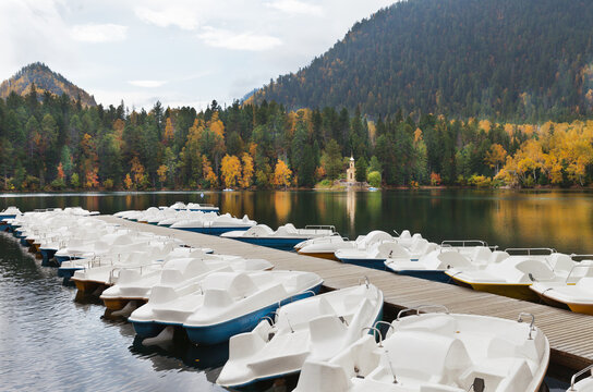Water bikes on the shores of picturesque warm Emerald Lake against the background of mountains with yellowed forest and beautiful Orthodox chapel of the Prophet Solomon on the opposite coast