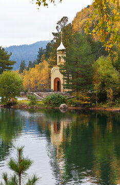 A picturesque autumn landscape with the Orthodox Chapel of the Holy Prophet Solomon on the shore of a warm Emerald Lake near the shore of Baikal  Lake on a foggy September day