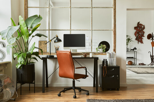 Stylish composition of modern masculine home office workspace interior design with black industrial desk, brown leather armchair, pc and stylish personal accessories. Template.