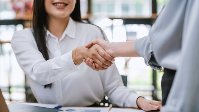 Close-up of business people shaking hands at the office success cooperation agreement.