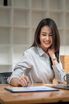 Image of a beautiful young Asian businesswoman having success working at the office.