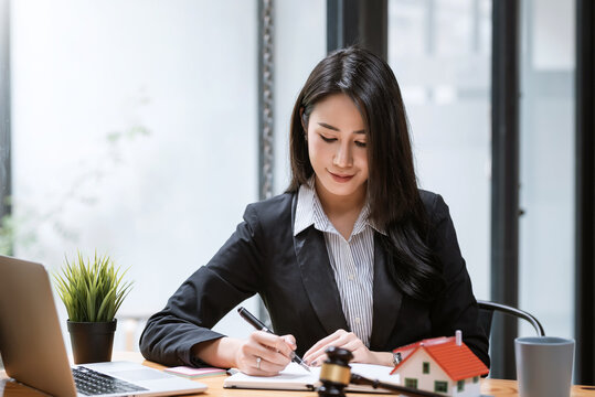 Young Asian businesswoman lawyer sitting at the courtroom holding a pen and taking notes on a table of house samples.