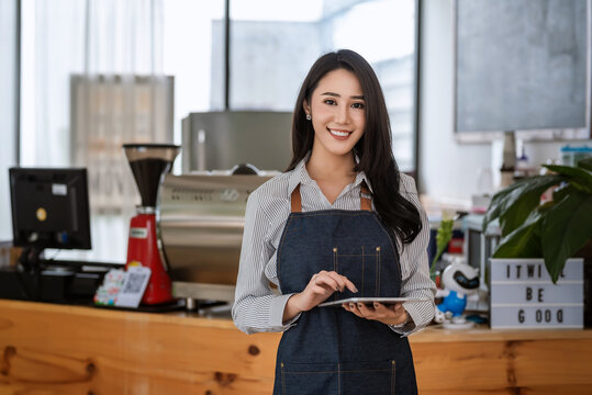 Young Asian businesswoman owner standing holding a tablet in front of a coffee shop cooking and beverage. Looking at the camera.