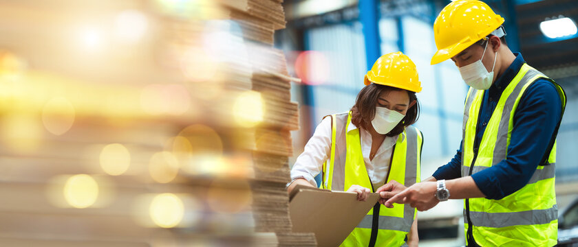 Asian male and female engineers wear protective gear and masks. Check the orderliness of the work within the warehouse.
