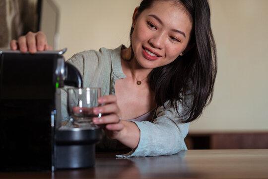Asian woman preparing hot drink in coffee machine