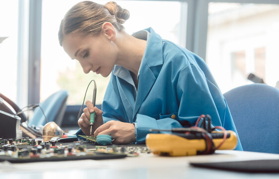 Worker in electronics manufacturing soldering a component for the prototype series by hand