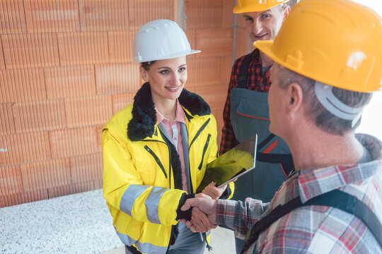Confident smiling female engineer in jacket and hardhat shaking hands with builder