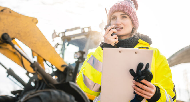 Woman with walkie talky on compost plant and wheel loader in background dispatching deliveries