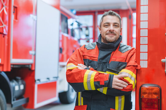Experienced fire fighter man standing in front of fire truck with arms crossed