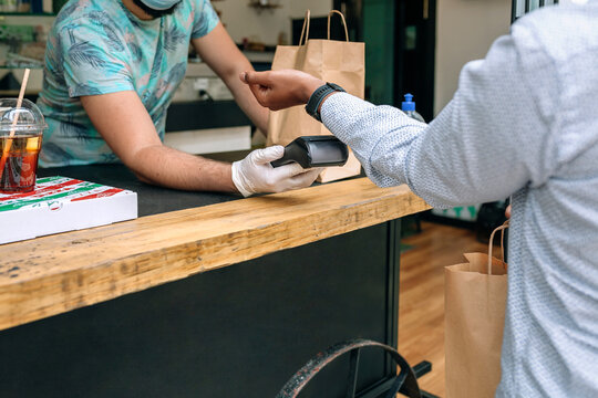 Detail of unrecognizable young man paying with smartwatch