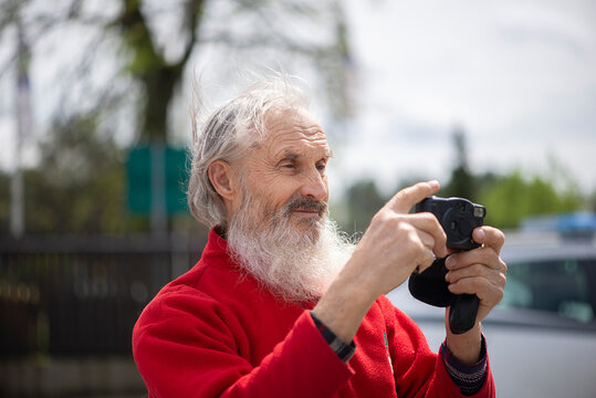 Close-up face portrait of bearded senior man photographer with old camera taking photo