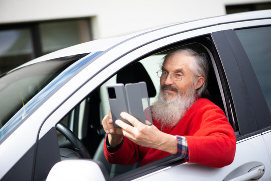 Bearded senior man with eyeglasses holding phone and texting while sitting in car a parking lot