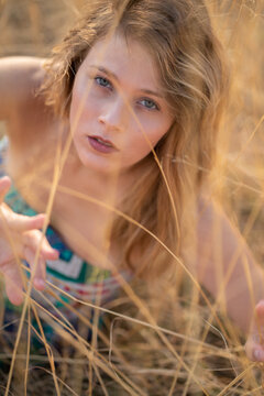 Natural Looking Young Beautiful Woman with Hazel eyes posing in the fields, no post editing