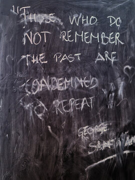 """Photo of a half washed out blackboard saying: """"Those wo do not remember the past are..."""" sorry my memory is a bit hazy."""