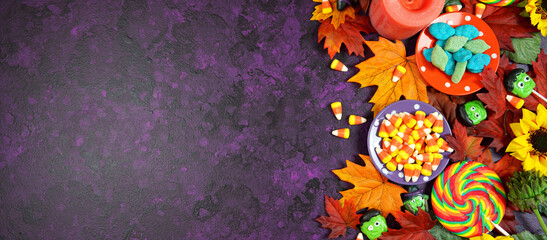 Obraz Halloween Trick or Treat Social Media Web Banner. Candy and lollipops, autumn leaves on stylish purple textured background. Top view blog hero header creative flat lay. Negative copy space. - fototapety do salonu