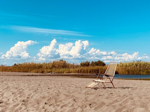 Deck Chairs On Sand At Beach Against Sky