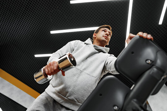 Determined handsome young male working out in gym with dumbbells