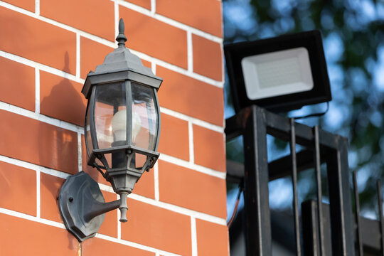 black vintage lamp on red brick wall. outdoor lamp wall.