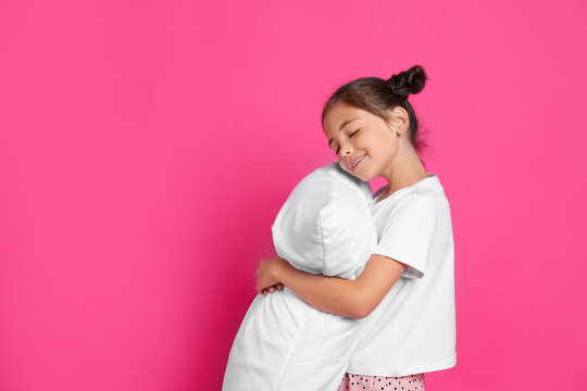 Cute girl in pajamas hugging pillow on pink background. Space for text