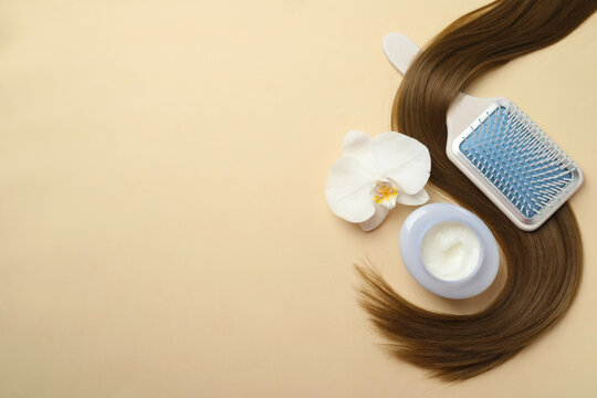 Jar of cosmetic product, orchid flower, brush and hair lock on beige background, flat lay. Space for text