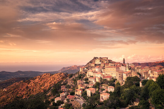 Sun setting on the remote mountain village of Speloncato in the Balagne region of Corsica with the Mediterranean sea in the distance