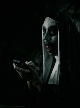 scary evil nun uses her smartphone
