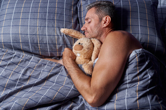 A young man sleeps in a hugging with a stuffed rabbit in bed.