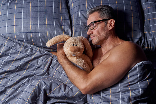 A young man sleeps with a stuffed rabbit in bed.