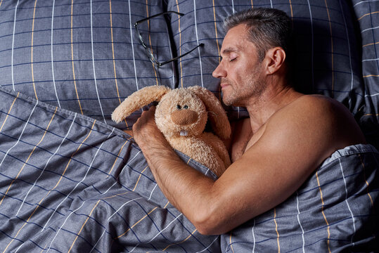 A young man sleeps in an embrace with a stuffed rabbit in bed with copy space.